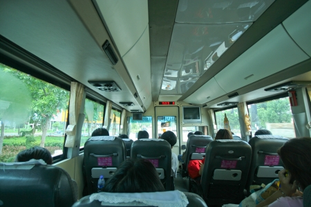 inside of a bus with passenger sitting in the seats