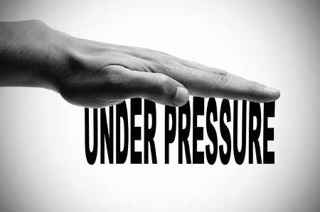 a man hand in black and white pressing the sentence under pressure written in black