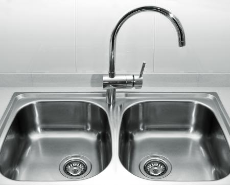 a double bowl stainless steel kitchen sink on a white granite worktop