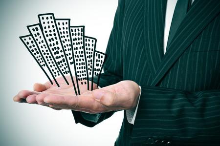 Photo pour a businessman showing a pile of drawn buildings in his hands - image libre de droit