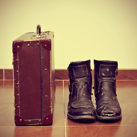 picture of an old suitcase and a pair of worn boots with a retro effect