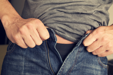 closeup of a young man trying to fasten his trousers, because of the weight gain