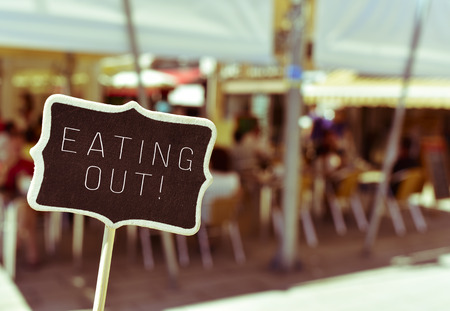 closeup of a chalkboard with the text eating out, in the busy terrace of a restaurant