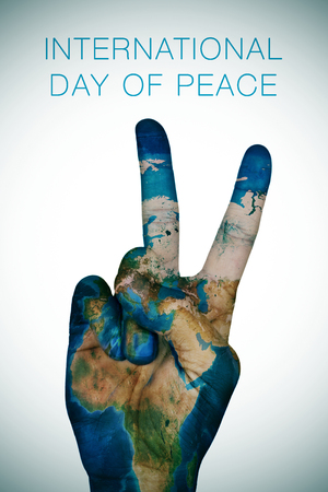 a man hand patterned with an Earth map  giving the V sign, as symbol of peace, and the sentence international day of peace
