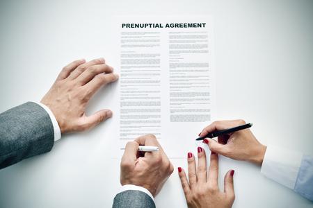 Photo pour closeup of a young man an a young woman signing a prenuptial agreement - image libre de droit