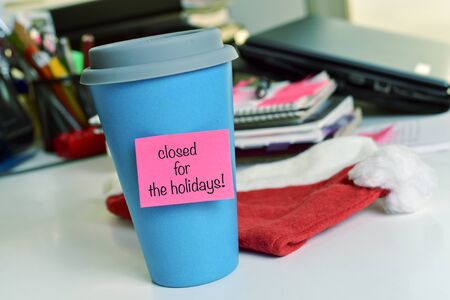 Photo for a blue mug with a pink sticky note with the text text closed for the holidays on an office desk - Royalty Free Image