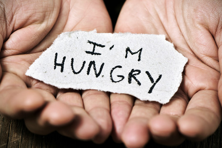 Photo for closeup of a piece of paper with the text I am hungry in the hands of a caucasian man - Royalty Free Image