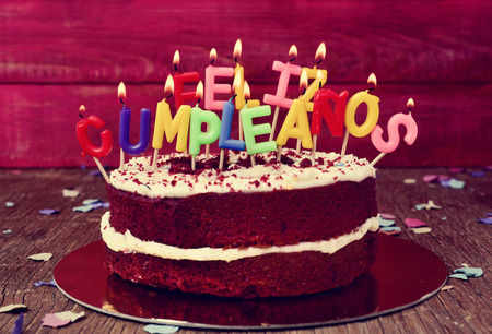 A Cake Topped With Some Lit Letter Shaped Candles Forming The Text Feliz Cumpleanos Happy Birthday In Spanish Before Blowing Out On Rustic