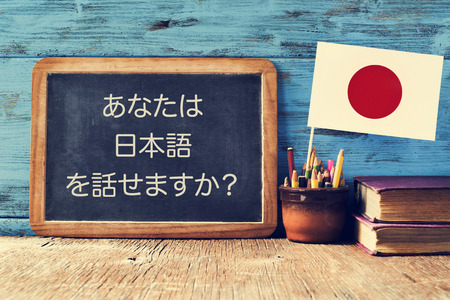 Photo pour a chalkboard with the question do you speak Japanese? written in Japanese, a pot with pencils, some books and the flag of Japan, on a wooden desk - image libre de droit
