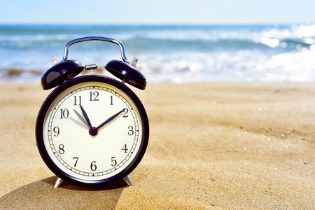Photo pour closeup of an alarm clock on the sand of a beach adjusting forward one hour at the beginning of the summer time - image libre de droit