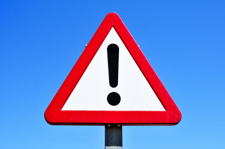 Photo pour a triangular traffic sign with an exclamation mark against the blue sky - image libre de droit