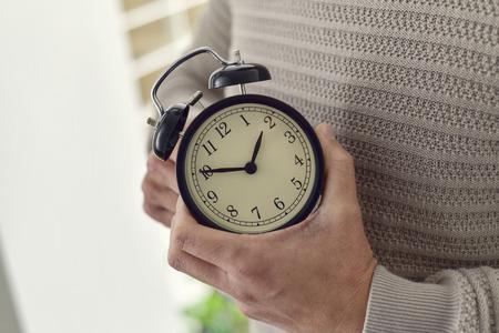 Photo pour closeup of young Caucasian man winding or adjusting the time of an alarm clock - image libre de droit