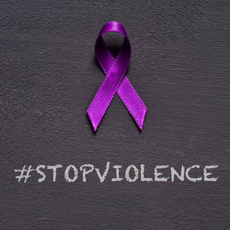 Photo pour closeup of a purple ribbon, for the awareness about the unacceptability of the violence against women, and the text stop violence on a dark gray background - image libre de droit
