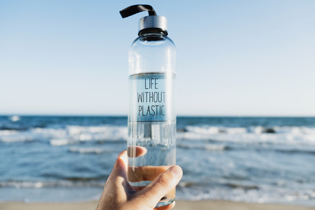 Photo for Closeup of a caucasian man holding a glass reusable water bottle with the text life without plastic written - Royalty Free Image