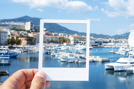Photo for closeup of a young caucasian man with a white frame in his hand, at the Port of Ajaccio, simulating an instant photograph - Royalty Free Image