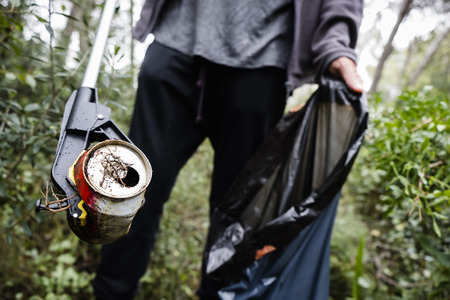 Photo pour closeup of a caucasian man collecting garbage with a trash grabber stick, in a forest, as an action to clean the natural environment - image libre de droit