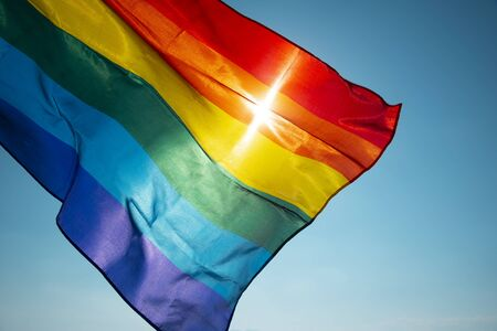 Photo pour closeup of a rainbow flag waving on the blue sky, moved by the wind, with the sun in the background - image libre de droit