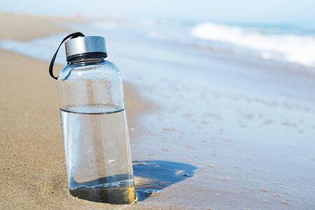 Photo pour closeup of a glass reusable water bottle on the seashore of a lonely beach - image libre de droit