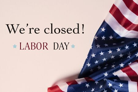 Photo pour some flags of the United States and the text we are closed, labor day, on a beige background - image libre de droit