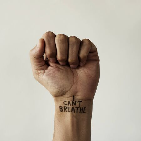 Foto per closeup of the raised fist of a man with the text I cant breathe in his wrist, as it is used as slogan in the protests in response to police brutality and racism in the United States - Immagine Royalty Free