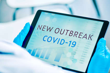 Foto de closeup of a doctor man, wearing blue surgical gloves, having a digital tablet in his hands with the text covid-19 new outbreak in its screen - Imagen libre de derechos