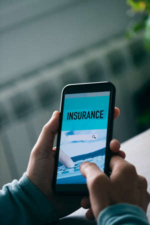 Photo for closeup of a young caucasian man, sitting at a table, searching an insurance online with his smartphone, with a simulated search engine - Royalty Free Image