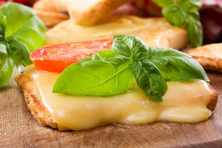 toast with melted cheese, tomato and basi