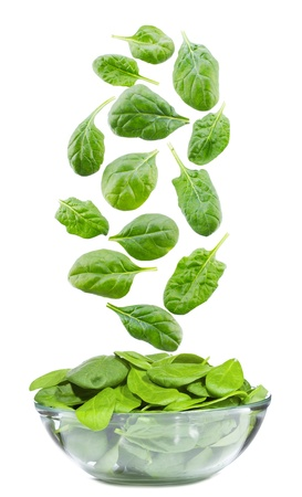 spinach leaves falling into bowl on white background