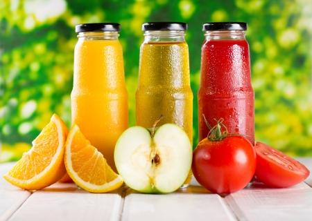 Photo pour different bottles of juice with fruits on wooden table - image libre de droit
