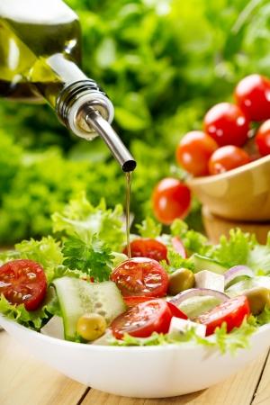Foto de olive oil pouring into bowl of salad - Imagen libre de derechos