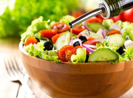 Foto de oil pouring into bowl of  salad - Imagen libre de derechos