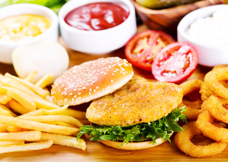 burger with chicken and fries on wooden table
