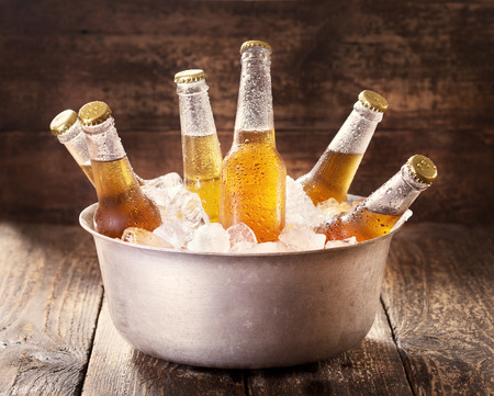 Photo pour cold bottles of beer in bucket with ice on wooden table - image libre de droit