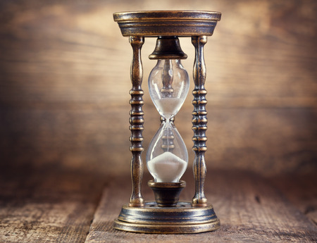old hourglass on wooden background