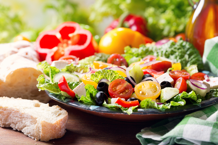 Foto de plate of greek salad on wooden table - Imagen libre de derechos