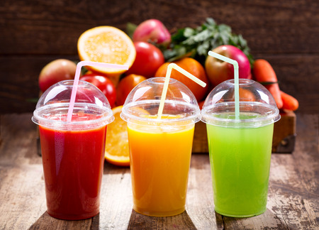 Fresh juices with fruits and vegetables on wooden backgroundの写真素材