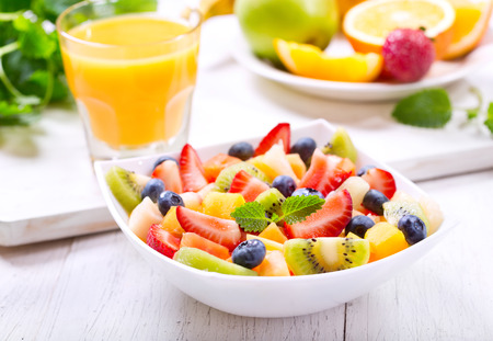 Foto de bowl of fruit salad on wooden table - Imagen libre de derechos