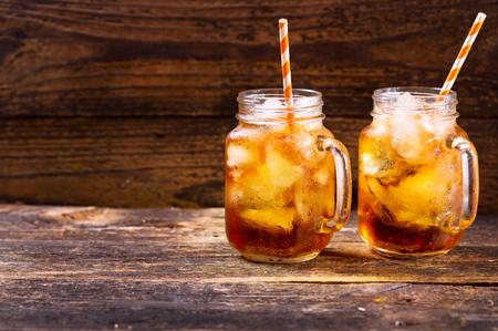 jars of peach iced tea on wooden table