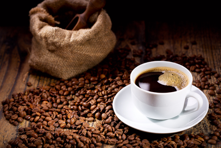 Photo pour cup of coffee with beans on wooden table - image libre de droit
