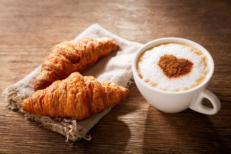 Photo pour Valentines day.  Cup of cappuccino coffee with drawn heart and fresh croissants on wooden table, top view - image libre de droit