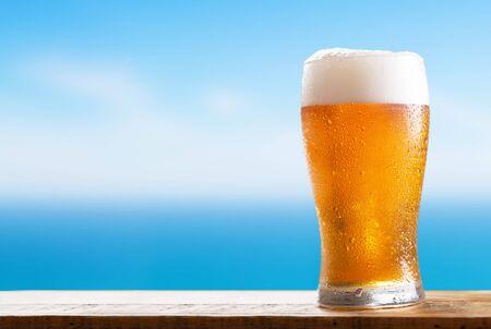 Foto de cold glass of beer on a wooden table on background of the sea - Imagen libre de derechos