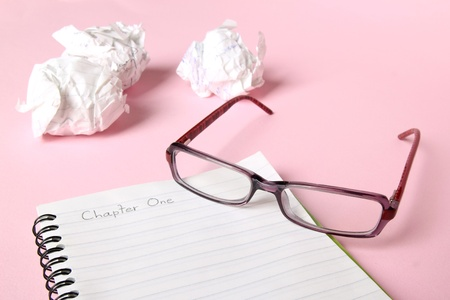 Concept of writer's block. Notebook with Chapter One written in it, with glasses and crumpled paper in the background.