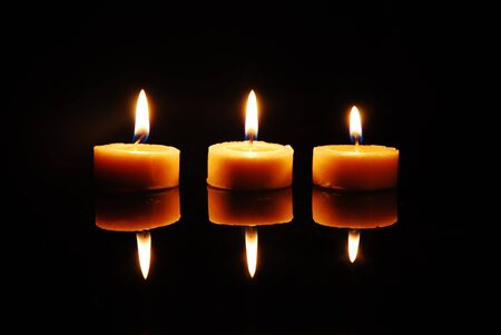 Three blazing wax candles standing in a line on a reflective plane