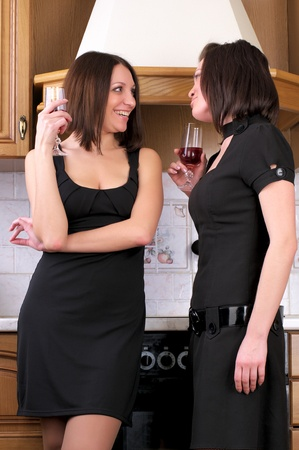 Two young beautiful women talking about something in the home kitchen with wine glasses
