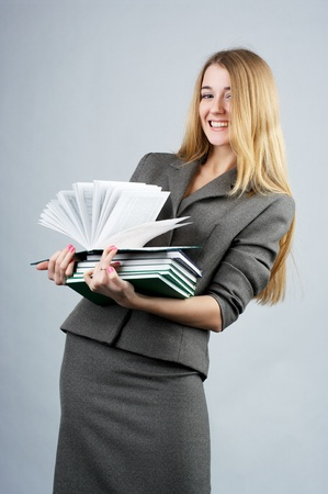 Portrait of a beautiful cheerful businesswoman with books