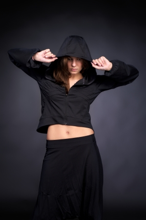Beautiful young woman in hip hop style with hood on the head against black wall