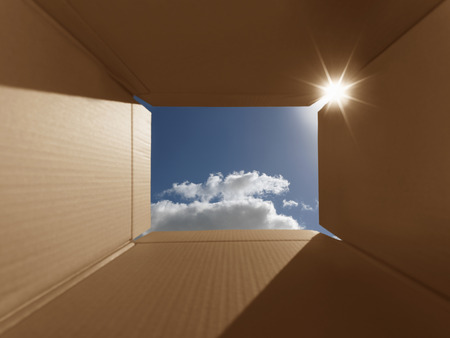 Photo pour Conceptual shot illustrating the phrase 'thinking outside the box'. Implies inspirational thoughts, bright new ideas, imagination and escaping from the norm. The box has areas for copy space. Carefully positioned to show the bright blue sky and also lens  - image libre de droit