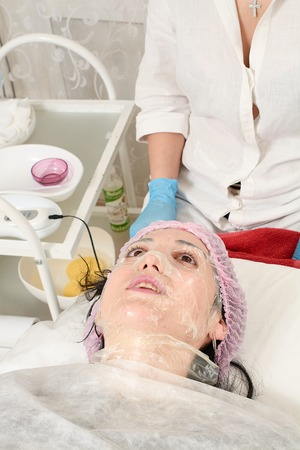 Photo for Young woman in beauty salon doing peeling and facial cleansing procedure. Cosmetic multifunctional device. Ultrasound procedure. Medical equipment healthcare. Face professional massage. - Royalty Free Image