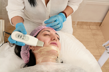 Young woman in beauty salon doing ultrasound peeling and facial cleansing procedure. Cosmetic multifunctional device. Ultrasound procedure. Medical equipment healthcare. Face professional massage.