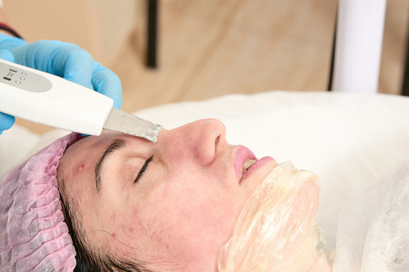 Photo for Young woman in beauty salon does ultrasound peeling and facial cleansing procedure. Cosmetic multifunctional device. Ultrasound procedure. Medical equipment healthcare. Face professional massage. - Royalty Free Image